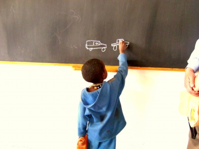 A young student showing off his artistic side with the rest of his class at one of imagine1day's schools